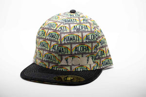 Adult flat brim snapback hat. Black flat brim. Panels have Hawaii license plates that say Aloha and Hawaii. Black Aloha Shapes® logo.