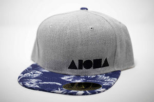 Adult flat brim snapback hat. Blue floral fabric on brim. Grey denim panels. Black embroidered Aloha Shapes® logo.