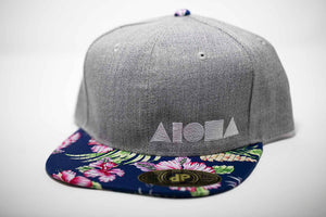 Adult flat brim snapback hat. Navy/pink floral pattern fabric on brim. Grey denim panels embroidered with white ALOHA Shapes ® logo