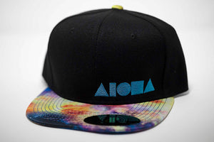 Adult flat brim snapback hat. Satin fabric with cosmic space print on brim. Black canvas panels. Turquoise embroidered Aloha Shapes® logo.