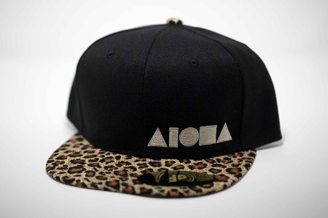 Adult Flatbrim snapback hat. Velvet cheetah print flat brim. Black canvas panels. Embroidered with cream color Aloha Shapes® logo.