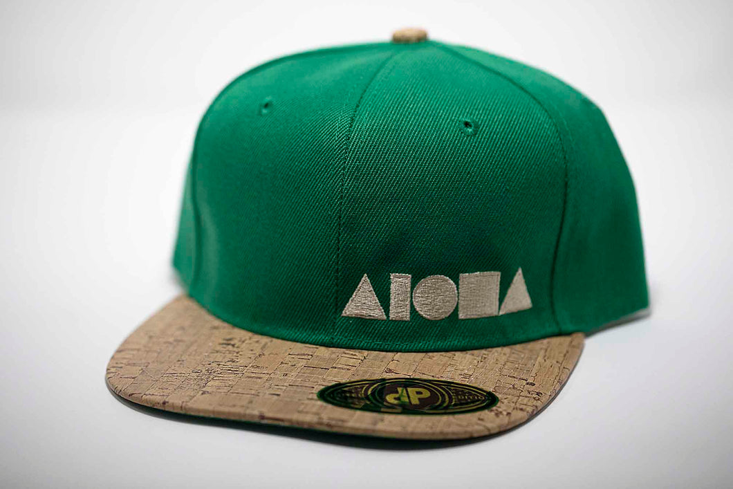 Adult flat brim snapback hat. Faux cork print on brim. Green canvas panels embroidered with cream ALOHA Shapes ® logo