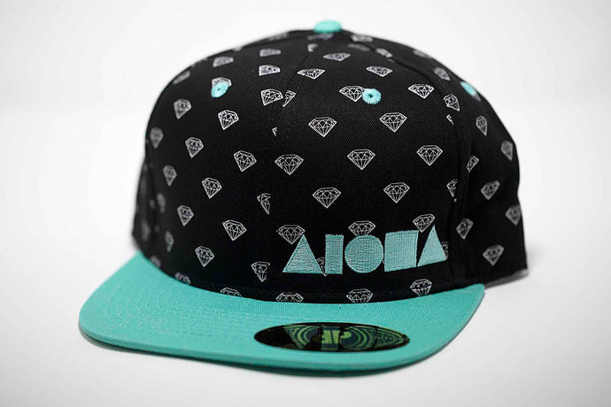 Adult flat brim snapback hat. Teal brim. Black fabric with white diamond pattern print on panels. Teal embroidered Aloha Shapes® logo.