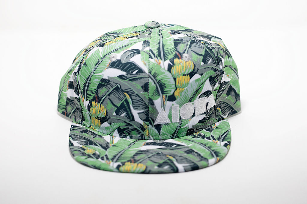 Youth flat brim snapback hat. Banana plant fabric all over hat. Embroidered with white ALOHA Shapes ® logo