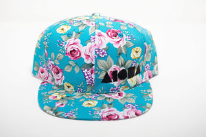 Youth flat brim snapback hat. Blue/pink/yellow floral print with roses all over hat. Embroidered with black ALOHA Shapes ® logo