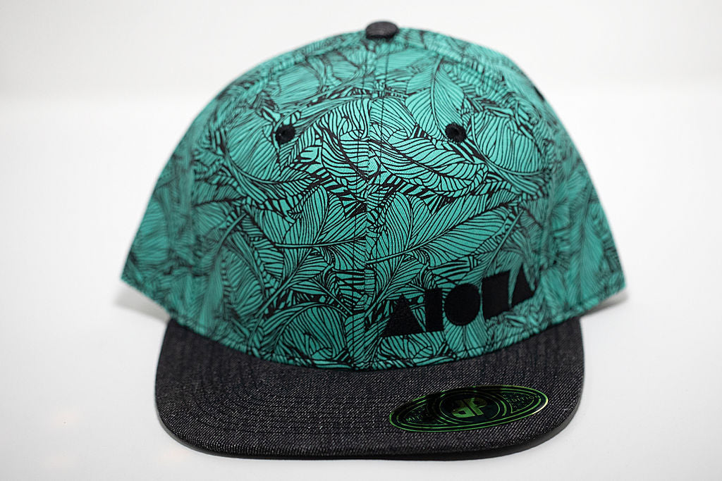Turquoise adult flat brim snapback hat with black tropical banana leaf pattern. Embroidered with black Aloha Shapes ® logo
