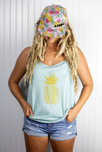 Blond dreadlocked girl wearing a pink pineapple adult snapback hat and a mint green pineapple tank top.