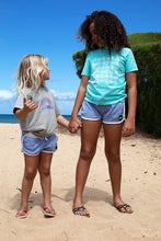 Two kids at beach holding hands and throwing shakes. One is wearing a Mint color Youth tee hand screenprinted with our Aloha Shapes® Basketweave pattern on front in white