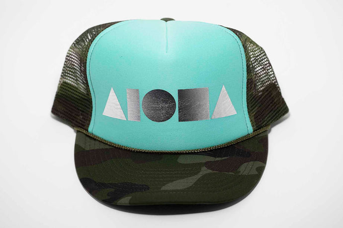 Aloha Shapes Adult Trucker Hat. Camo bill and mesh back. Seafoam green front panels foil printed with metallic silver logo