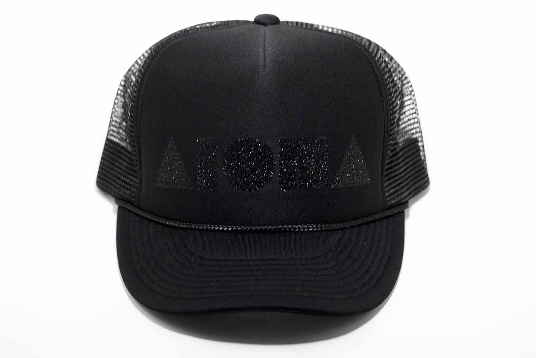 Aloha Shapes logo in black sparkles printed on an all black youth trucker hat