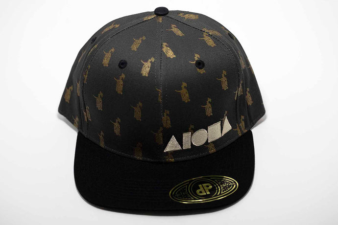 Adult flat brim snapback hat stamped with King Kamehameha and embroidered with Aloha Shapes ® logo