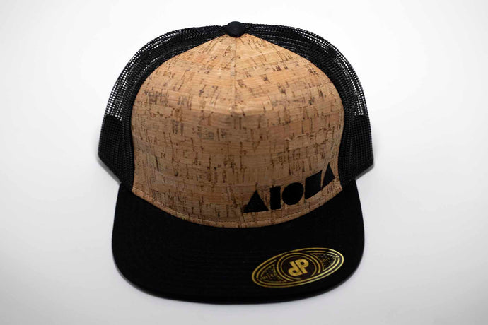 Adult flat brim snapback hat. Black canvas brim. Real cork material on front panels embroidered with our black Aloha Shapes® logo. Black mesh back panels.