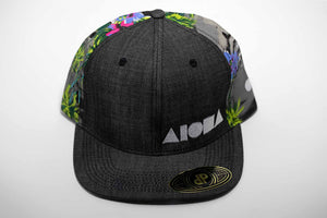 Adult flat brim snapback hat with black denim and multi-colored tropical flower and palm tree fabric. Embroidered with white Aloha Shapes ® logo