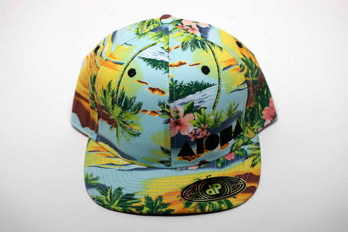Adult flat brim snapback hat with tropical paradise fabric all over. Embroidered with black Aloha Shapes ® logo