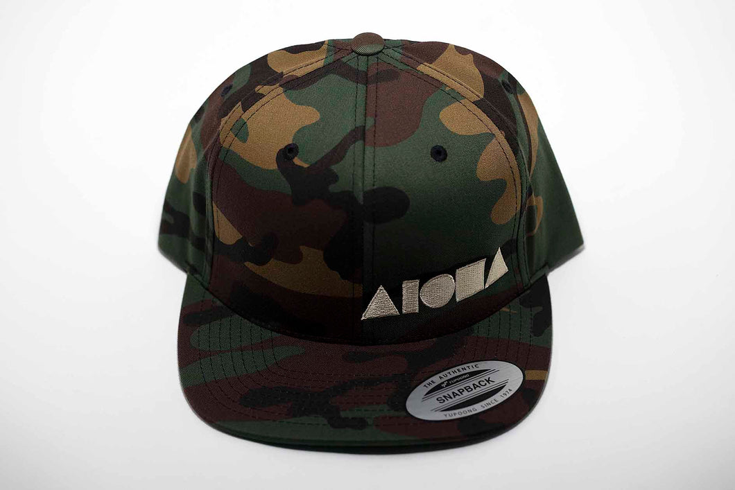 Adult flat brim snapback hat in woodland camo pattern embroidered with cream color Aloha Shapes ® logo