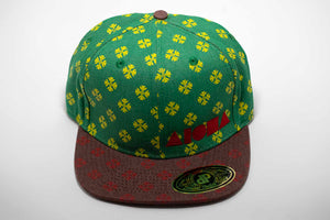 Adult flat brim snapback hat. Red flat brim. Green and yellow hawaiian quilt kahili pattern on panels. Embroidered with red Aloha Shapes® logo.