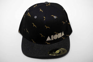 Adult flat brim snapback hat. Black denim brim. Black fabric panels with gold Hawaiian iwa bird pattern. Embroidered with white ALOHA Shapes ® logo