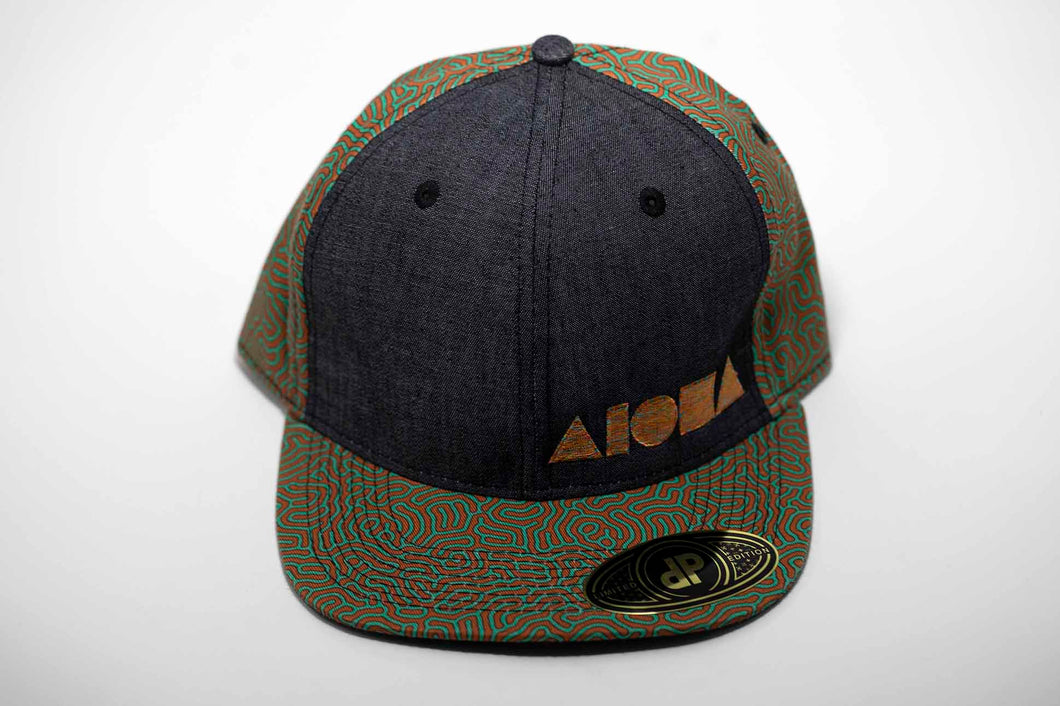 Adult flat brim snapback hat. Orange/teal coral reef pattern fabric on brim and back panels. Grey denim front panels. Multi-color embroidered Aloha Shapes® logo