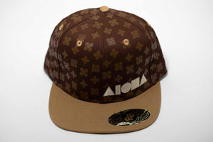 Adult flat brim snapback hat. Tan color brim. Brown fabric with Hawaiian quilt pattern on panels. A take on the classic Louis Vuitton print. Embroidered with tan ALOHA Shapes ® logo