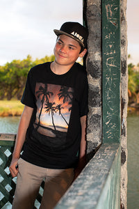Teenage boy wearing black t-shirt with photo of palm trees and Maui sunset on it.