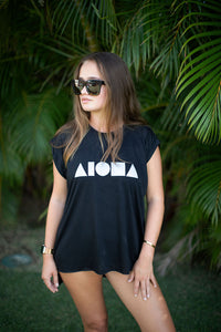 Young woman wearing a Black Aloha Shapes ® flowy muscle tee and dark sunglasses in front of palm trees