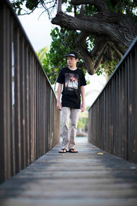 Teenage boy walking down narrow boardwalk wearing black t-shirt with photo of palm trees and Maui sunset on it.