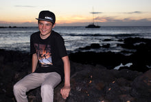 Teenage boy sitting on seawall by ocean wearing black t-shirt with photo of palm trees and Maui sunset on it.