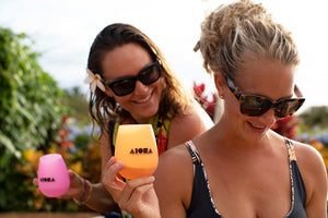Two beautiful women in swimsuits drinking wine from silicone ALOHA Shapes ® logo beach cups