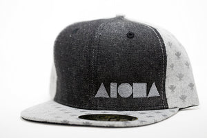 Adult flat brim snapback hat. Grey canvas with Hawaiian kahili pattern on flat brim and back panels. Black denim front panels with silver embroidered Aloha Shapes® logo.
