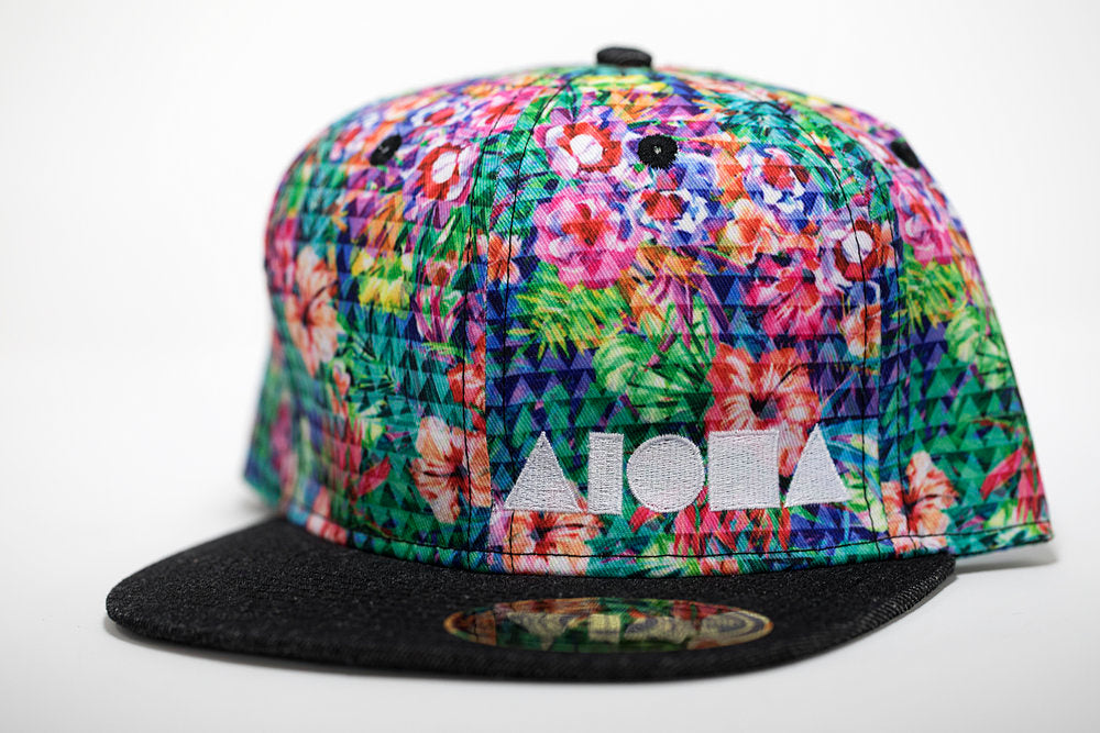 Adult flat brim snapback hat. Black denim brim. Floral print fabric overlaid with triangles on panels. Embroidered with white Aloha Shapes® logo.