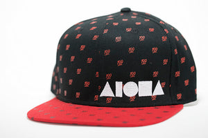 Adult flat brim snapback hat. Red flat brim. Black panels with red 100 emojis. White Aloha Shapes® logo.