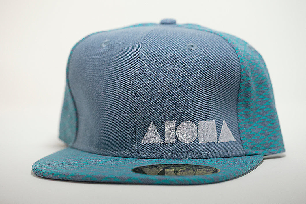 Adult flat brim snapback hat. Grey denim printed with blue triangle pattern on brim and back panels. Front panel plain grey denim with white ALOHA Shapes ® logo embroidered.