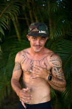 Man with tattoos wearing a camouflage print Aloha Shapes ® snapback hat in front of palm trees