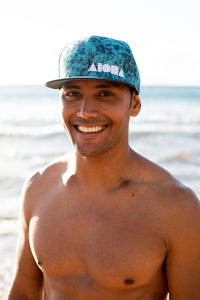 Handsome young man with no shirt wearing an ALOHA Shapes ® logo snapback hat on the beach.