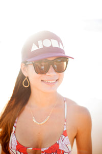 Young woman in the sunlight wearing an ALOHA Shapes ® logo maroon/silver trucker hat.