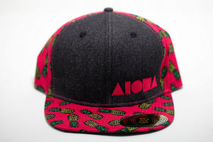 Adult flatbrim snapback hat. Neon pink fabric with pineapple print on brim and back panels. Grey denim front panels embroidered with neon pink ALOHA Shapes ® logo