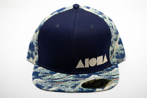 Adult flat brim snapback hat. Navy blue front panel embroidered with white ALOHA Shapes ® logo. Brim and back panels are printed with Japanese waves from old woodblock paintings.