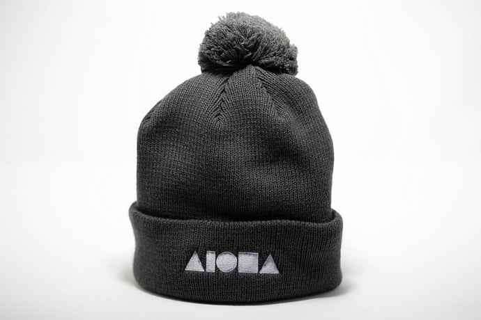Adult beanie cap with poof top in grey. Embroidered with white ALOHA Shapes ® logo