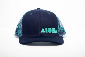 Adult curved bill snapback hat with navy blue front panels and teal colored kalo leaves printed on back mesh panels. Embroidered on front with teal Aloha Shapes ® logo