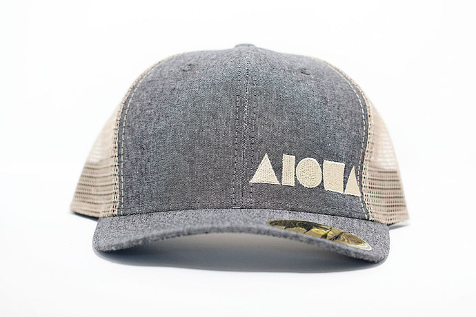Adult curved bill snapback with grey denim bill and front panels, cream color back mesh panels. Embroidered on front with cream Aloha Shapes logo