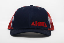 Adult curved bill snapback hat with navy blue panels on front and Hawaiian flag printed on back mesh panels. Embroidered on front with red Aloha Shapes logo