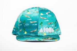 Adult flatbrim snapback hat with blue satin fabric printed with airplanes, aloha, Pacific and palm trees all over. Embroidered with white Aloha Shapes logo