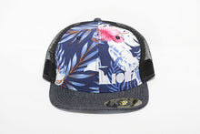 Adult flat brim snapback hat. Black denim flat brim. Blue and pink floral pattern front panels. Black mesh back panels. Embroidered with white Aloha Shapes® logo.