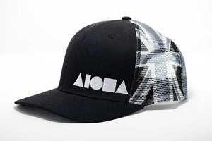 Side view Limited edition adult curved bill snapback. Black brim and front panels. Greyscale Hawaiian flag printed on mesh back panels. Embroidered with white Aloha shapes ® logo