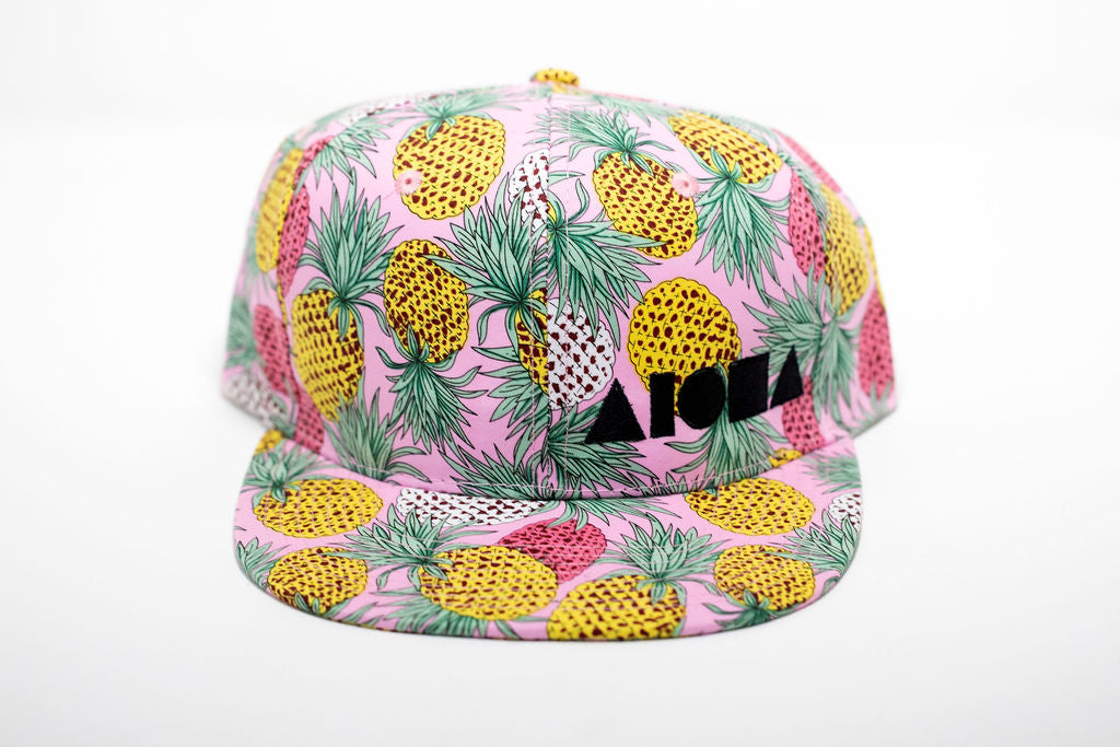Pink pineapple adult snapback hat with white, yellow and pink pineapples all over. Embroidered with black Aloha Shapes ® logo