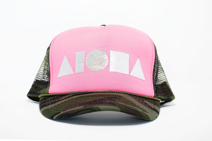 Adult trucker with camo print brim and mesh back panels and neon pink front panels. Foil printed on front with metal silver Aloha Shapes logo