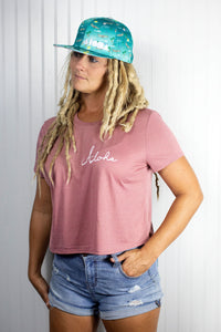 Woman with blond dreadlocks wears Adult flatbrim snapback hat with blue satin fabric printed with airplanes, aloha, Pacific and palm trees all over. Embroidered with white Aloha Shapes logo