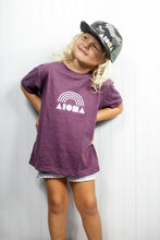 Adorable little blond girl wearing Aloha Shapes® Rainbow tee and camo print flat brim snapback hat