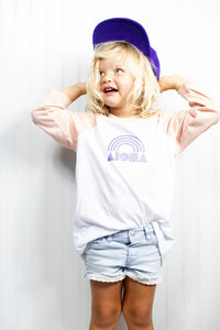 Young happy blond girl wearing an Aloha Shapes® Rainbow youth baseball t-shirt printed in Maui, Hawaii