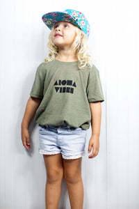 young blond girl wearing Aloha Vibes youth t-shirt and snapback hat